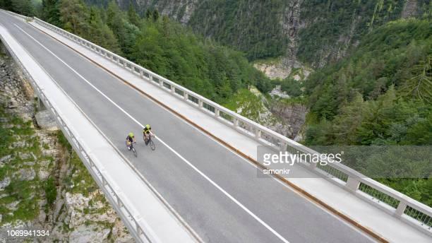 two men riding road bikes on bridge - tracciatura stradale foto e immagini stock