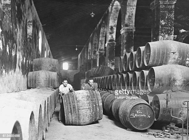 Two men roll an empty barrel or butt out of the large warehouse of the bodega of the Sanchez Romate at JerezdelaFrontera Spain A blender will begin a...