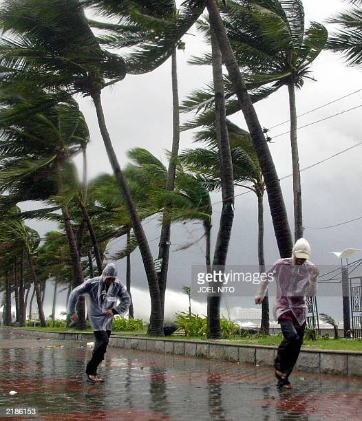 Two men run from strong winds whipping up huge waves along Manila Bay 22 July 2003 as Typhoon Imbudo slammed in northern Philippines At least five...