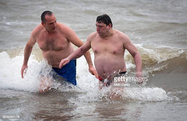 Two men run into the sea as they take part in the annual New Year's Day swim at Barry Island as several hundred swimmers marked start of 2016 by...