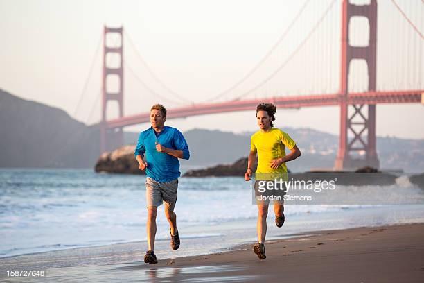 Two men running during sunset.
