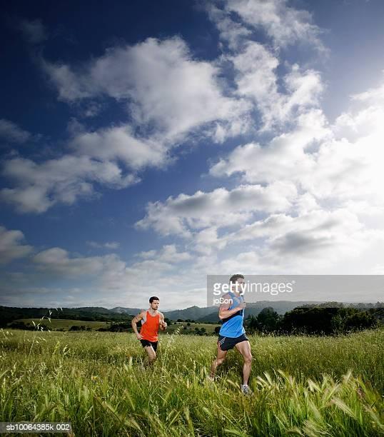 Two men running through grass