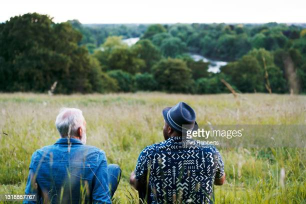 two men sat, looking at view - talking stock pictures, royalty-free photos & images