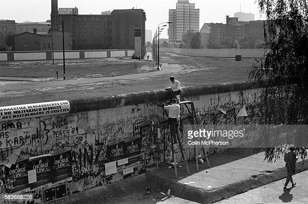 Two men scaling the Berlin Wall during a protest at a section of the wall at the Brandenburg Gate West Berlin The Berlin Wall was a barrier...