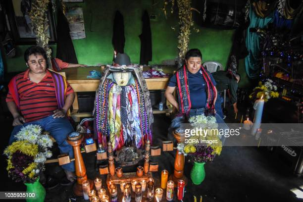 Two men seen sitting next to an idol during a traditional catholic ceremony to venerate the god of the region 'Maximon' in Santiago Atitlan Guatemala