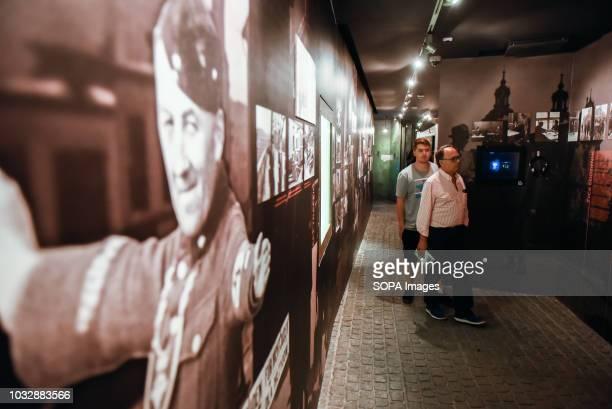 Two men seen walking through one of the exhibition rooms during the exhibition Exhibition at Oskar Schindler's Enamel Factory museum it is primarily...