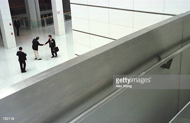 Two men shake hands September 18 2000 in the lobby of the World Bank headquarters main complex in Washington DC