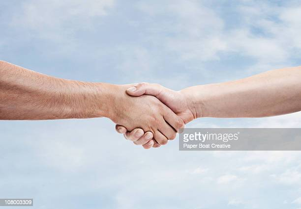 two men shaking hands againt sky background - handshake stock pictures, royalty-free photos & images