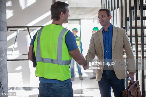 Two men shaking hands on construction site