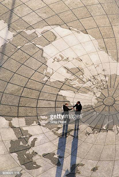 Two men shaking hands on world map, patterned paved area