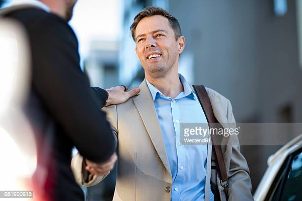 two men shaking hands outdoors - hand on shoulder stock pictures, royalty-free photos & images