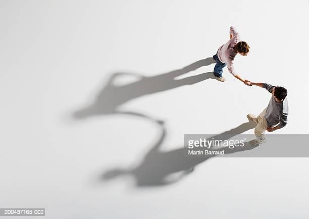 two men shaking hands, overhead view - accord concepts photos et images de collection
