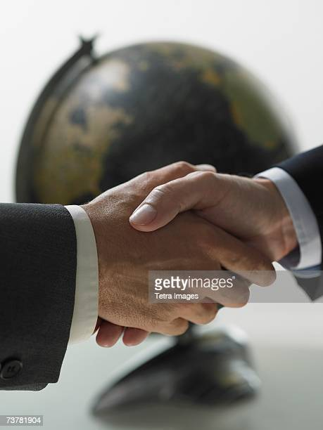 Two men shaking hands with globe in background
