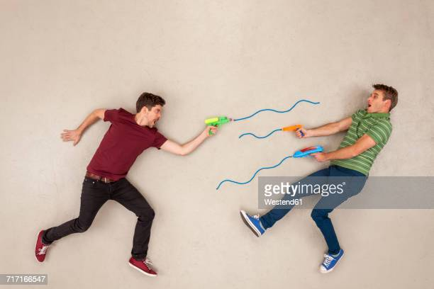 Two men shooting each other with toy guns