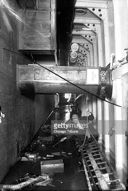 Two men sift through the water looking for bodies inside the SS Eastland as it rests on its side in the Chicago River after slowly rolling over and...