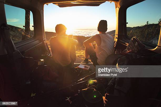 Two men siiting in car watching sunset