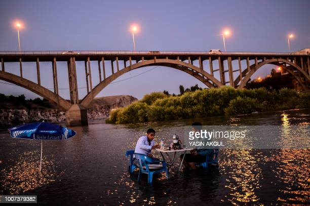 Two men sit at a table placed in the waters of the Tigris River that runs through the 12000yearold Hasankeyf settlement and ancient citadel town...