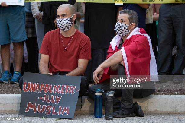 """Two men sit besides a sign reading """"Unapologetic Ally Muslim"""" at the London Muslim Mosque during the multi-faith march to end hatred, after a man..."""
