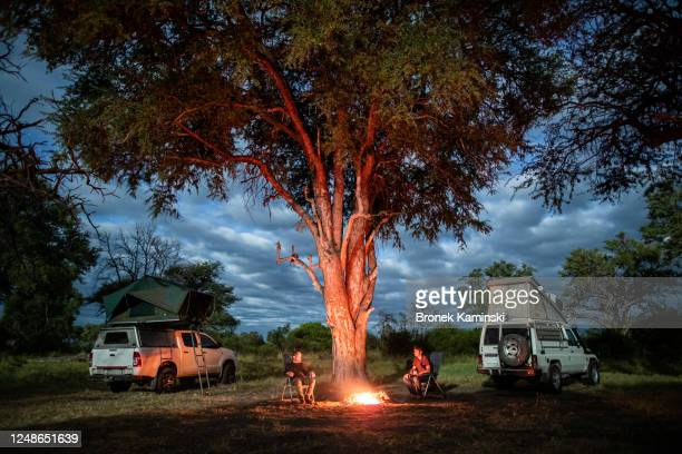 two men sit by a campfire in the african bush - night safari stock pictures, royalty-free photos & images