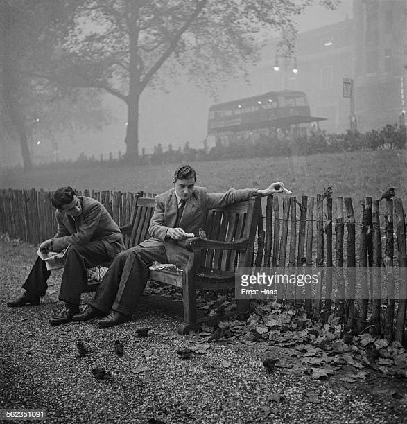 Two men sit on a bench feeding birds in Green Park London circa 1953