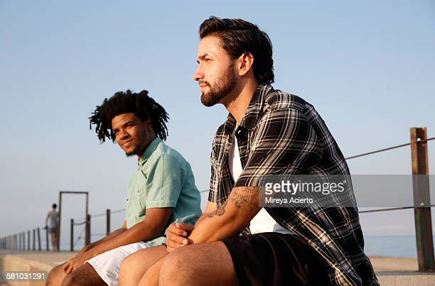 Two ethnic men sit on a pier by the beach