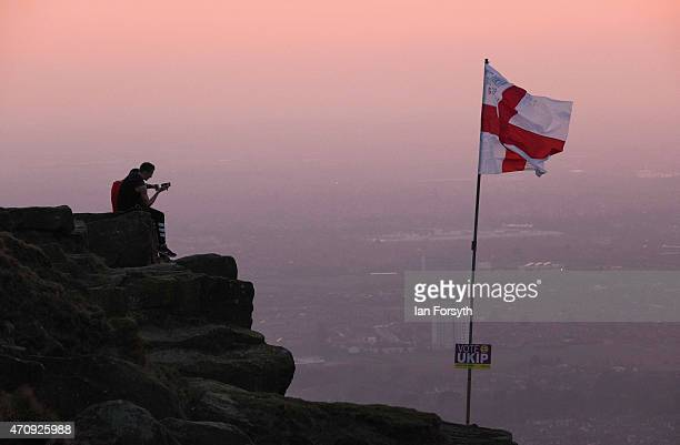 Two men sit on a rock outcrop next to a flag pole flying a St George flag on the top of Eston Nab a local landmark overlooking Teesside on April 24...