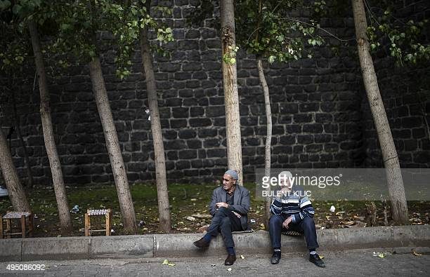 Two men sit under trees in the district of Sur in Diyarbakir, southeastern Turkey, on October 31, 2015 on the eve of the country's general election....