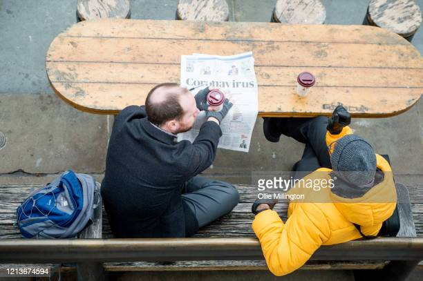 Two men sit with coffees at lunchtime in Trafalgar Square on March 19 2020 in London England