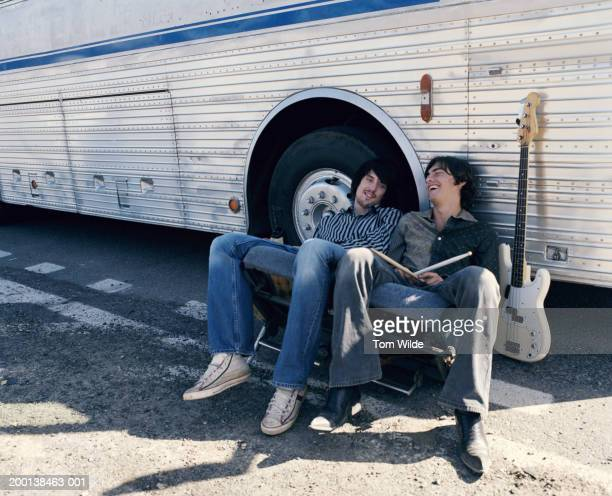 Two men sitting against coach next to guitar, one holding drumsticks
