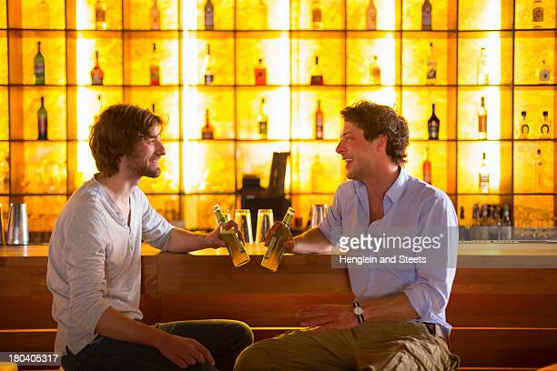 Two men sitting at bar with bottles of beer