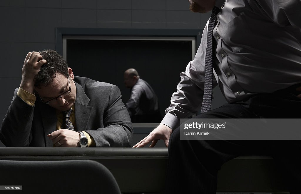 Two men sitting at desk in interrogation room : Stock Photo