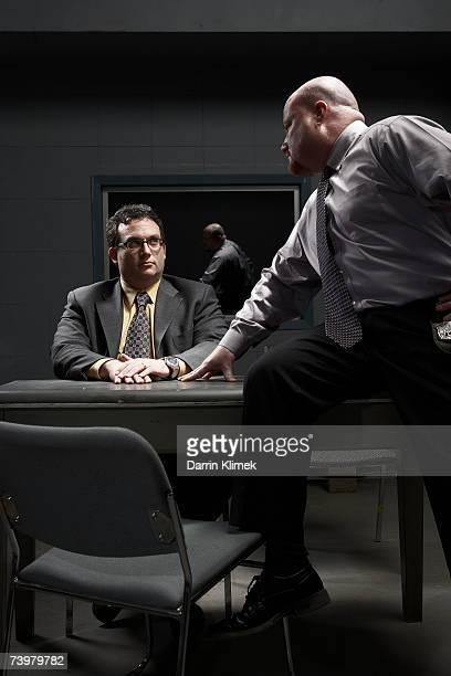 Two men sitting at desk in interrogation room