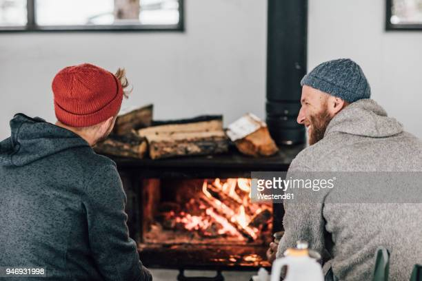 two men sitting at fireplace - hygge stock pictures, royalty-free photos & images