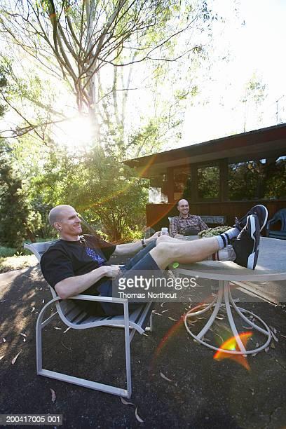 zwei männer sitzen am tisch auf der terrasse, lachen - shorts stock-fotos und bilder