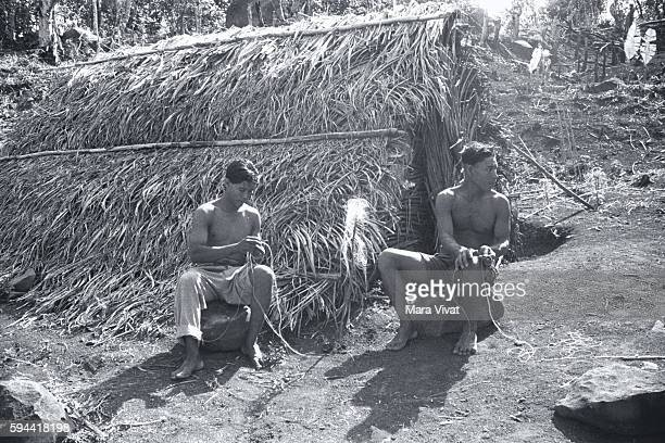 Two Men Sitting By Hut Braiding Rope Dominica