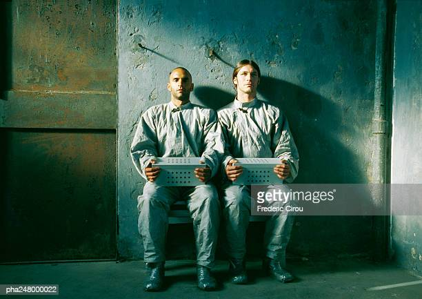 Two men sitting, holding boxes
