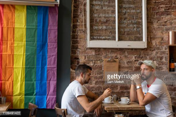Two men sitting in a coffee shop on the day of the Brighton Pride parade on the 3rd August 2019 in Brighton in the United Kingdom