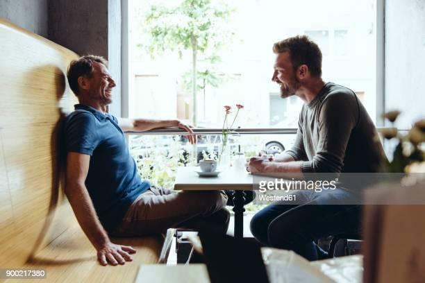 two men sitting in cafe talking to one another - männerfreundschaft stock-fotos und bilder
