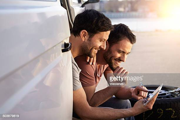 Two men sitting in car looking at digital tablet