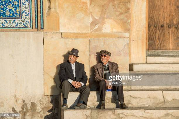 two men sitting in front of sheikh lotfollah mosque, isfahan - isfahan province stock pictures, royalty-free photos & images