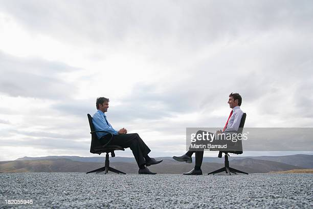 Two men sitting in office chairs outdoors