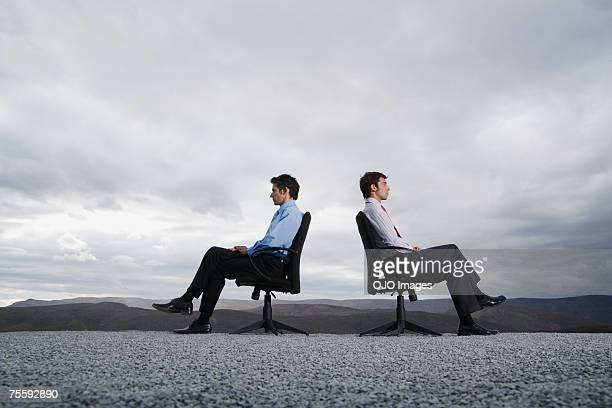 two men sitting in office chairs outdoors with their backs against one another - confrontation stock pictures, royalty-free photos & images