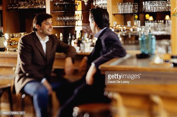 Two men sitting in pub, talking, smiling