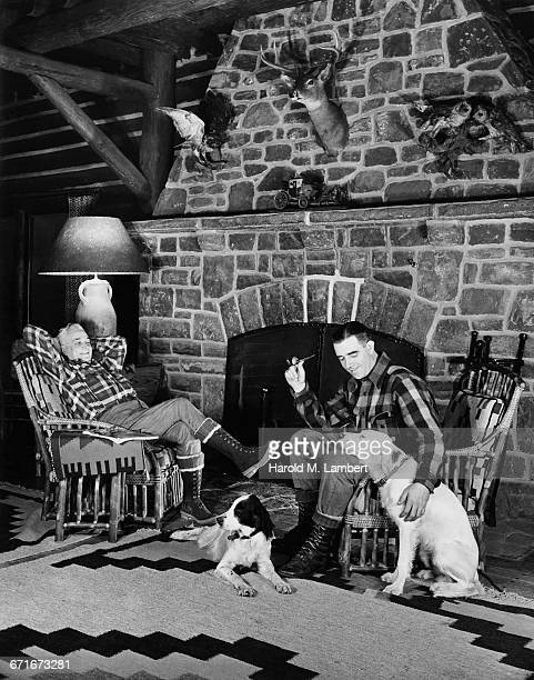 """two men sitting on chair near fireplace, looking at dog "" - pawed mammal stock pictures, royalty-free photos & images"