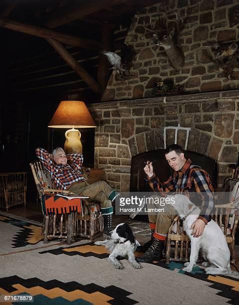 """""""two men sitting on chair near fireplace, looking at dog  """" - mamífero con garras fotografías e imágenes de stock"""