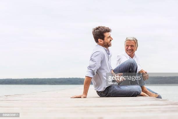 Two men sitting on pier, relaxing, smiling