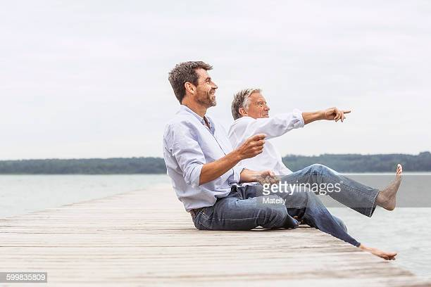 Two men sitting on pier, throwing stones, smiling