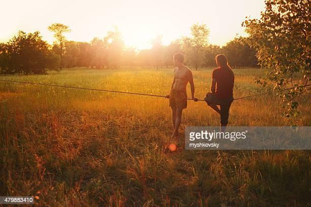 2 人の男性が座っ slackline in the meadow 夕暮れ時です。