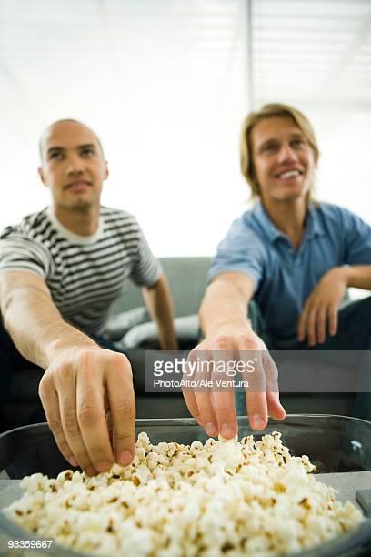 Two men sitting on sofa eating popcorn