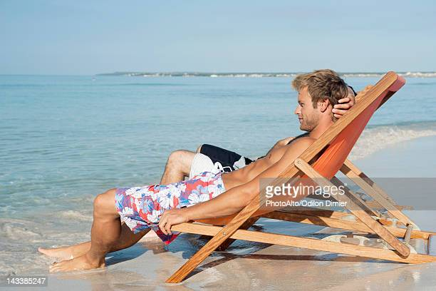 Two men sitting side by side on beach looking at ocean